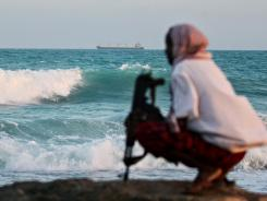 A Somali pirate watches the coastline near Hobyo, northeastern Somalia, in 2010.