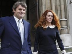 Rebekah Brooks, former chief executive of News International, and her husband, Charlie Brooks, leave the High Court in London on Tuesday.