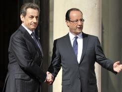 France's president Nicolas Sarkozy, left, welcomes his successor, Francois Hollande, upon his arrival at the Elysee Palace for the formal handover of power ceremony on Tuesday.