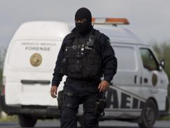 A federal policeman guards the area where dozens of bodies were found on a highway connecting Monterrey, Mexico, to the U.S. border Sunday.