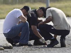 Forensic experts examine the area where dozens of bodies were found on a highway near the city of Monterrey, Mexico, on Sunday.