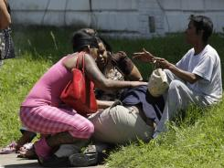 A woman is overcome with grief at the scene of a triple shooting in Louisville.