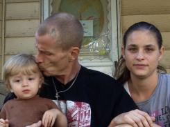 McKinley Woodby holds his 15-month-old son, Damien, as the boy's mother Erin Fink joins them on the front steps of their Cleveland home. A blood test had recently found that Damien had an elevated level of lead in his body, health department records show.