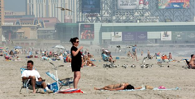 People relax on the beach in Atlantic City, N.J., on April 16, well before the typical summer weather season.