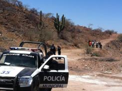 Police secure the area where the body of Mexican police reporter Marco Antonio Avila Garcia was found inside a black plastic bag on the side of a road in Sonora, Mexico, on Friday.