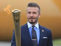 David Beckham holds the Olympic Flame after its arrival Friday in Cornwall, England.