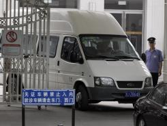 A van with covered windows leaves in a convoy Saturday under tight security from the hospital where blind activist Chen Guangcheng was recuperating in Beijing.