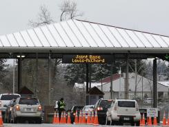 Guards check the identification of drivers passing through a gate at Joint Base Lewis-McChord.