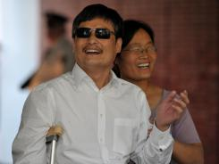 Blind Chinese activist Chen Guangcheng and his wife, Yuan Weijing, smile upon their arrival at the New York University Village apartment complex in Manhattan on Saturday.