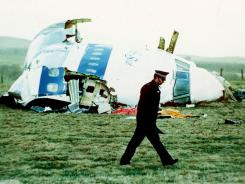 A police officer walks by Pan Am Flight 103 on Dec. 21, 1988, in a field near Lockerbie, Scotland. A bomb aboard the plane exploded.