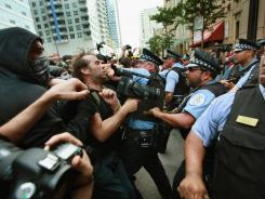 Police clash with demonstrators protesting the NATO summit during a march through downtown streets on Sunday in Chicago.