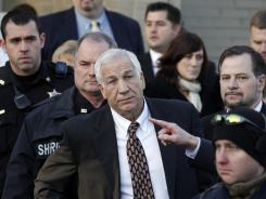Jerry Sandusky, center, leaves the Centre County Courthouse in Bellefonte, Pa.