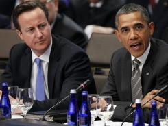 President Obama, accompanied by British Prime Minister David Cameron, speaks Monday during the final day of the NATO summit in Chicago.