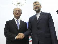 Iran's top nuclear negotiator, Saeed Jalili, right, shakes hands with IAEA chief Yukiya Amano in Tehran, May 21.