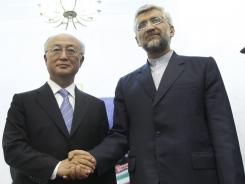 Iran's top nuclear negotiator, Saeed Jalili, right, shakes hands with International Atomic Energy Agency chief Yukiya Amano after meeting Monday in Tehran.