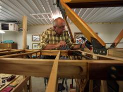 Tom Vukonich works on a De Havilland DH-4B wooden bi-plane in his garage in Metamora, Mich. The NTSB approved recommendations for the FAA and Experimental Aircraft Association to improve safety.