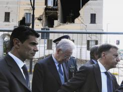 Italian Premier Mario Monti, center, walks Tuesday past the damaged town hall of Sant'Agostino during a visit to the area hit by a quake.
