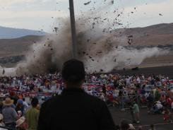 In this Sept. 16, 2011, photo, A P-51 Mustang airplane crashes into the edge of the grandstands at the Reno Air show in Reno, Nev.