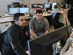 Michael Cantor, 28, left, and Nathan Grossman, 25, work in the war room of American Bridge 21st Century in Washington.