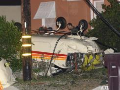 Investigators look over a single-engine plane which crashed in the front yard of a home in Glendale, Calif.