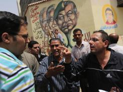 Egyptians argue political issues in front of an anti-government mural Tuesday, a day before presidential elections in Cairo, Egypt.