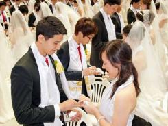 A couple exchanges rings during a mass wedding ceremony arranged by the Unification Church in Korea on March 24.