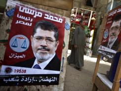 A man walks by posters of a Muslim Brotherhood presidential candidate in Cairo on Tuesday.