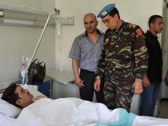 Members of the U.N. Syrian mission visit a wounded man at the Tishreen Military Hospital in Damascus.