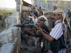 Armed fighters of the people's resistance force of Lawder battle to push al-Qaeda-linked militants out of their town in Abyan province, Yemen.