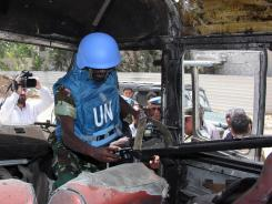 A U.N. observer takes pictures of a military bus that was damaged by a roadside bomb near Damascus on Wednesday.