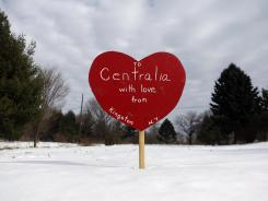 A wooden heart with the words &quot;To Centralia with Love from Kingston N.Y.&quot; stands in an open lot in Centralia, Pa.