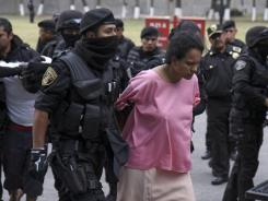 Maria del Carmen Rios Garcia is escorted by police after being taken into custody in Toluca, Mexico, May 24.