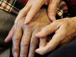 Shou-Mei Li holds the hand of her husband, Hsien-Wen Li, who is an Alzheimer's patient, at their home in San Francisco last year.