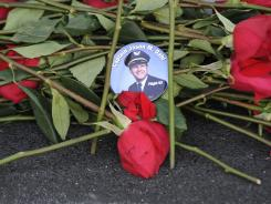 Roses and a memorial badge are placed below the name of Capt. Jason Dahl on the Flight 93 Memorial wall during the dedication of the memorial in Shanksville, Pa.
