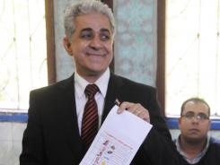 Third-place Egyptian presidential election finisher Hamdeen Sabahi, showing his paper ballot after voting this week, has called for a recount.