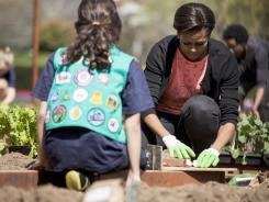 Michelle Obama and a schoolgirl work in the White House garden.