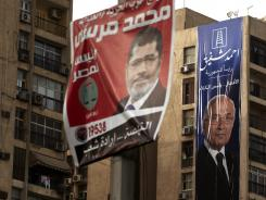 Campaign posters supporting presidential candidates Mohammed Morsi, left, and Ahmed Shafiq, right, hang in Cairo on Monday.