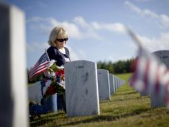 Cathy Ridge visits the grave of her husband, Charles Ridge, a retired Marine, on Monday in Canton, Ga.