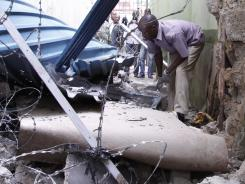A Kenyan police officer inspects building damage after an explosion Monday in Nairobi.