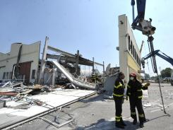 Firefighters inspect a collapsed factory in Mirandola, Italy, after a quake Tuesday.