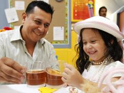 Luis Rodriguez and daughter, Chloe, 3, clink glasses during the 10th annual Tea Party and 70th Birthday Celebration at the Mary McLeod Bethune Day Nursery in Corpus Christi, Texas. The event provides an opportunity for parents to bond with their children.
