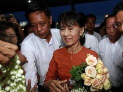 Aung San Suu Kyi receives flowers from supporters Tuesday as she arrives at an airport in Burma.