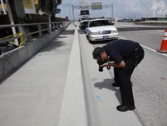 Crime Scene investigator Andres Betancourt photographs a credit card found at the scene belonging to Rudy Eugene on Tuesday in Miami.