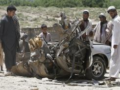 Afghans look at a damaged vehicle after it was hit by a roadside bomb inJalalabad east of Kabul. Three workers died in the attack.
