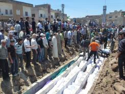 Houla massacre: Syrians watch a mass burial May 26.