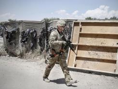 A NATO-led International Security Assistance Force member walks toward the police checkpoint in Jalalabad, Afghanistan.
