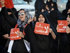 Bahraini Shiite Muslim women hold posters as they demonstrate Thursday in solidarity with political prisoners in the village of Abu Saiba, west of Manama.