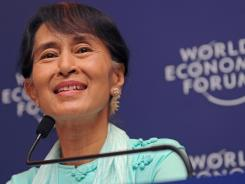 Aung San Suu Kyi smiles while answering a question Friday during a press conference in Bangkok.