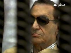 An image grab taken from Egyptian state TV shows ousted Egyptian president Hosni Mubarak sitting inside a cage during his verdict hearing in Cairo.