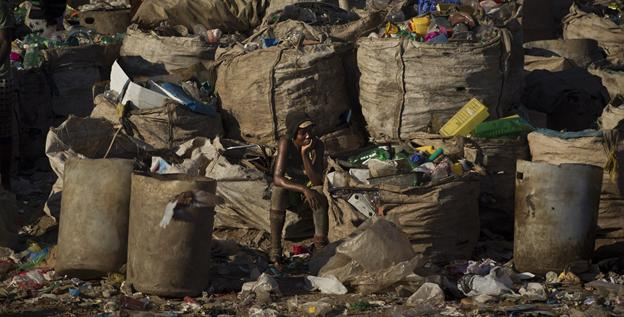 A woman rests among sacks filled with recyclable materials at the Jardim Gramacho, one of the world's largest open-air landfills.